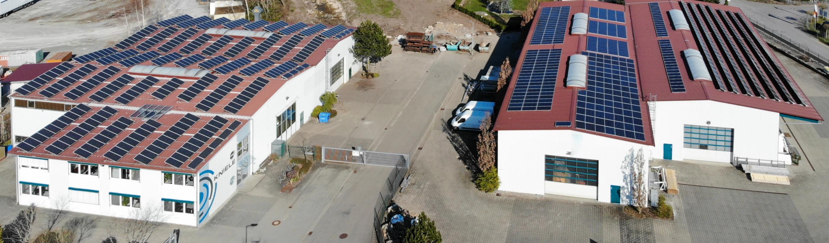 Vogelperspektive der Fertigungshallen von Kniele mit PV-Anlage auf dem Dach, Kniele Logo am Verwaltungsgebaeude.