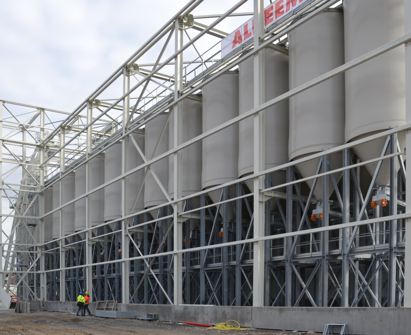 Deux hommes devant un système de plusieurs silos blancs habillés et avec une structure de support en acier.